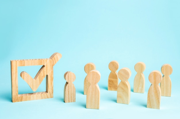 Menselijke figuren staan samen naast een vinkje in de doos. het concept van verkiezingen