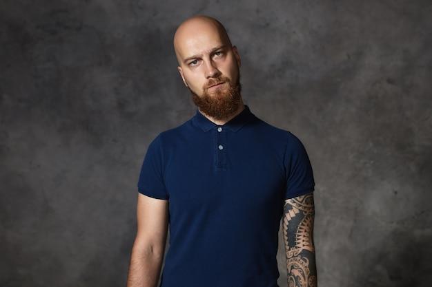 Menselijke gemakkelijke uitdrukkingen. taille-up shot van stijlvolle europese hipster man met getatoeëerde arm en bijgesneden gemberbaard starend met een ontevreden blik, vol minachting, wantrouwend