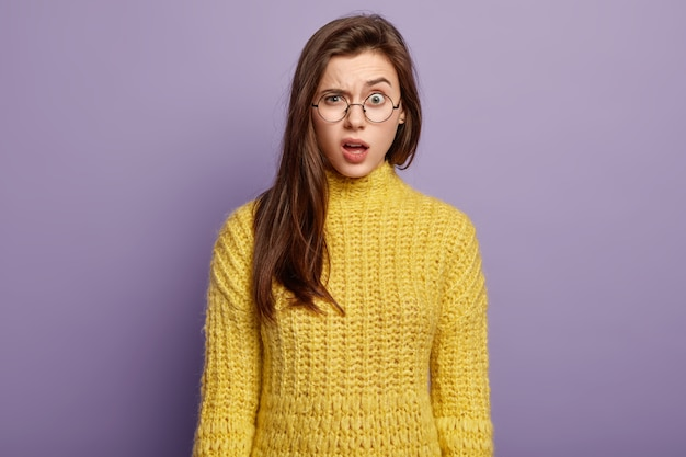 Menselijke gezichtsuitdrukkingen concept. mooie vrouw met verontwaardigde verbaasde blik, hoort schokkend nieuws van gesprekspartner