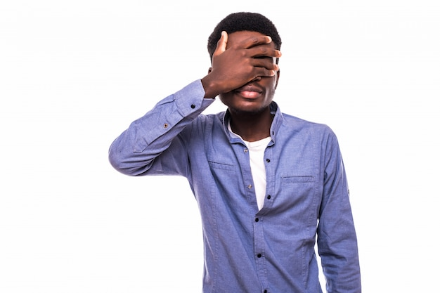 Menselijke gezichtsuitdrukkingen, emoties en gevoelens. jonge afro-amerikaanse man met geruit hemd over wit t-shirt, gezicht bedekkend met hand, spijt of schaamte, wil zijn ogen niet laten zien