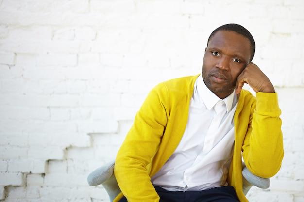 Menselijke gezichtsuitdrukkingen, emoties en gevoelens. knappe afrikaanse man met triest teleurgestelde blik, hand op zijn gezicht houden, zittend in een stoel op witte bakstenen muur met kopie ruimte voor uw tekst