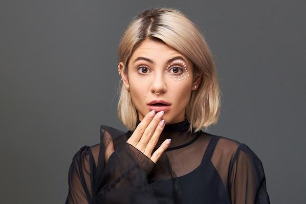 Menselijke gezichtsuitdrukkingen, emoties en gevoelens. prachtige schattige europese vrouw met blond haar die oprechte verrassing en shock uitdrukt, haar mond opent en ogen uittrekt, vol ongeloof is