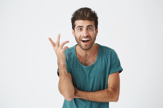 Menselijke gezichtsuitdrukkingen, emoties en gevoelens. verbaasd en verrast bebaarde jonge man in blauw t-shirt wijzend op blinde muur, vertellen dat hij een idee heeft