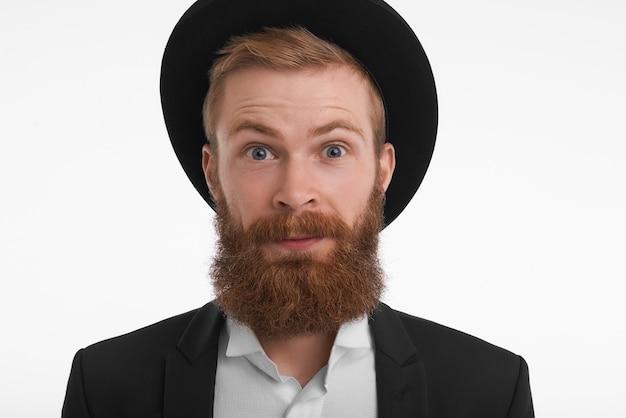 Menselijke gezichtsuitdrukkingen, emoties, gevoelens en reacties. grappige emotionele jonge europese bebaarde man in zwarte ronde hoed en jas die zijn wenkbrauwen opheft, verrast en geschokt is met nieuws