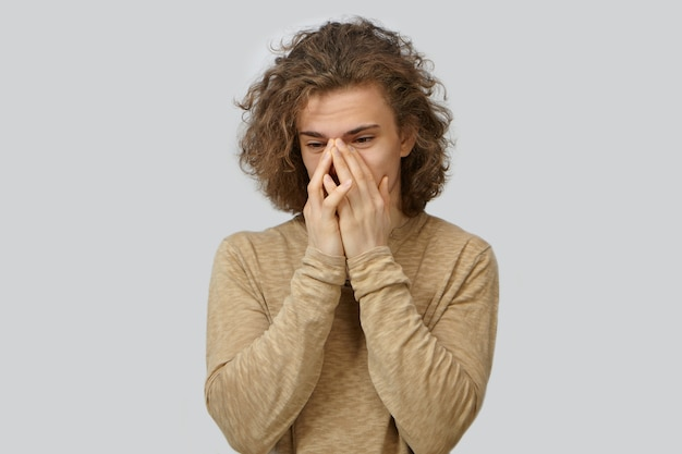 Menselijke gezichtsuitdrukkingen, emoties, gevoelens, reacties en lichaamstaal. geïsoleerde portret van knappe stijlvolle student man met krullend haar voor zijn mond, vergeetachtig blik te hebben benadrukt