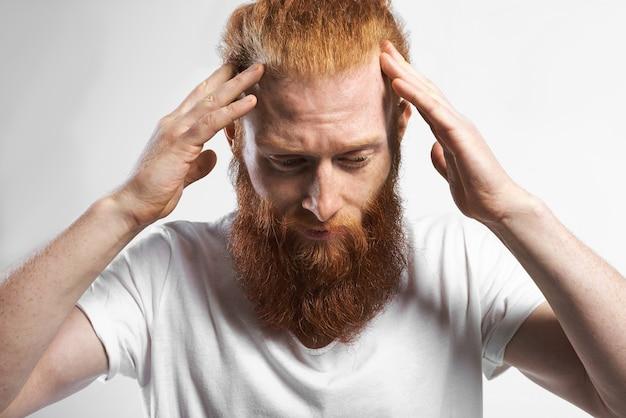 Menselijke gezichtsuitdrukkingen, emoties, reactie en houding. portret van gefrustreerde jonge blanke bebaarde man die gestrest voelt, een probleem heeft, naar beneden kijkt, hand in hand op zijn hoofd