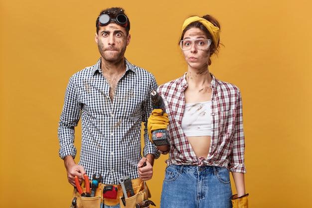 Menselijke gezichtsuitdrukkingen en emoties. binnen schot van verbaasde jonge mannelijke elektricien die riem draagt die met instrumenten wordt gebreid