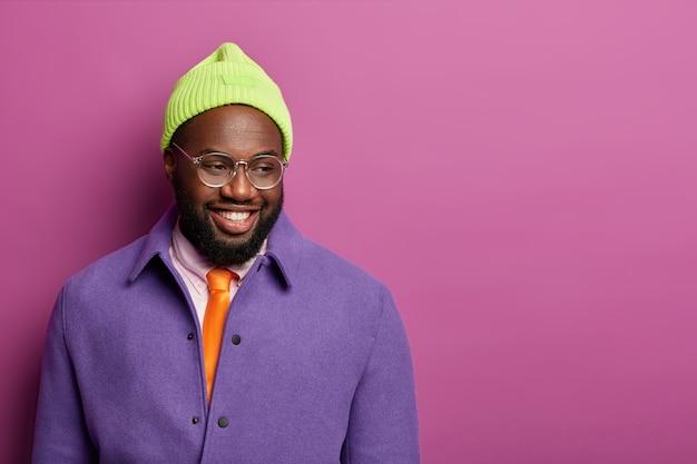 Menselijke gezichtsuitdrukkingen en emoties concept. knappe zwarte man met vrolijke uitdrukking, neerkijkt, denkt aan iets aangenaams
