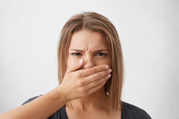 Menselijke gezichtsuitdrukkingen en emoties. headshot van bang jonge vrouw met bob-kapsel dat haar mond bedekt met hand alsof ze niets mag zeggen, kijkend met ogen vol angst