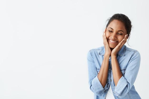 Menselijke gezichtsuitdrukkingen en emoties. jonge afro-amerikaanse vrouw met zwart haar en gesloten ogen, glimlachend met plezier, hand in hand op haar wangen, met een gelukkige en kalme uitdrukking van het gezicht.