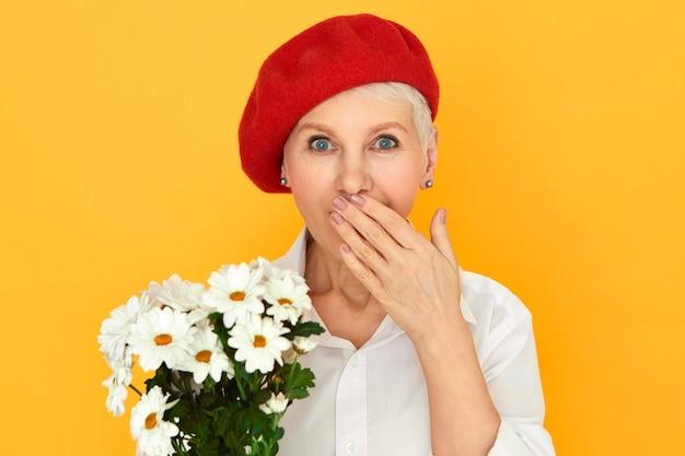 Menselijke gezichtsuitdrukkingen en emoties. portret van blauwogige kortharige vrouw in elegante hoofddeksels die de mond bedekken terwijl hij naar adem snakt