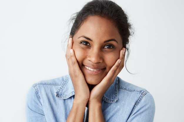 Menselijke gezichtsuitdrukkingen en emoties. portret van jonge afro-amerikaanse vrouw in lichtblauw denim shirt op zoek gelukkig, met haar hoofd met beide handen, met een glimlach.