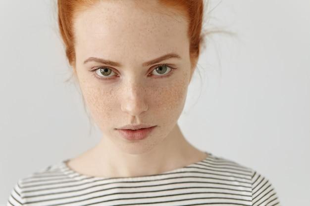 Menselijke gezichtsuitdrukkingen en emoties. portret van jonge roodharigevrouw in zeemansoverhemd die zeker ernstig gezicht hebben, geïsoleerd stellen