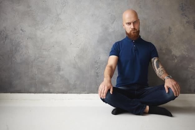 Menselijke gezichtsuitdrukkingen en lichaamstaal. emotionele knorrige jonge ongeschoren bebaarde man met geschoren hoofd zittend op de vloer benen gekruist houden, boos zijn terwijl niet kan ontspannen, proberen te mediteren