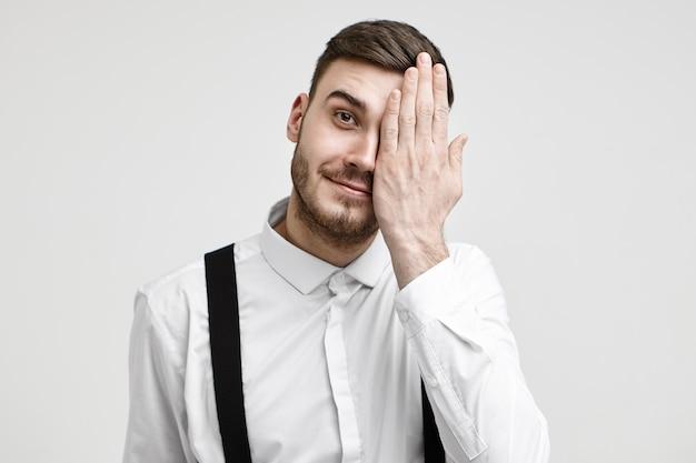Menselijke gezichtsuitdrukkingen en lichaamstaal. geïsoleerde schot van positieve jonge bebaarde zakenman die de ene helft van zijn gezicht bedekt en vrolijk lacht naar de camera. optica, visie, gezichtsvermogen en oftalmologie