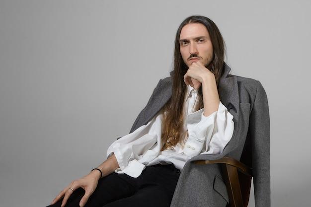 Menselijke gezichtsuitdrukkingen en lichaamstaal. portret van bebaarde langharige jonge europese man in trendy modieuze kleding comfortabel in stoel zitten