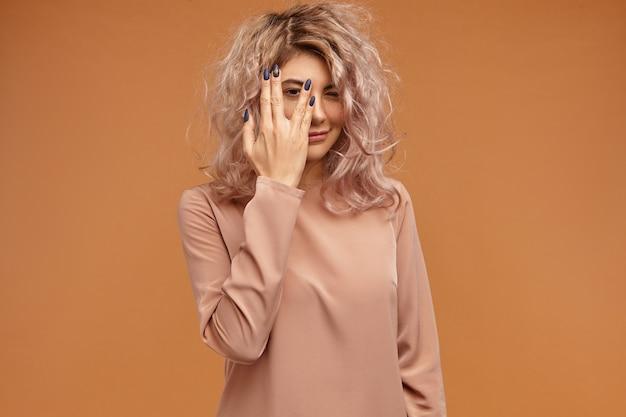 Menselijke gezichtsuitdrukkingen en lichaamstaal. portret van modieus hipstermeisje met slordig roze haar en zwarte lange spijkers die gezicht behandelen