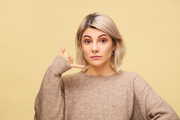 Menselijke gezichtsuitdrukkingen en lichaamstaal. positieve knappe jonge blonde vrouw die hand aan zijn oor houdt en mobiele telefoon imiteert, zeggend bel me, ik zal contact houden, geïsoleerd poseren