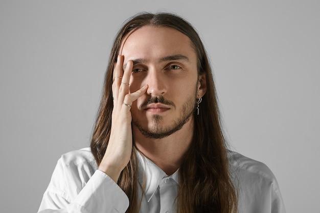 Menselijke gezichtsuitdrukkingen. geïsoleerde shot van knappe ongeschoren jonge blanke man met lang haar poseren, serieus kijken, hand op zijn gezicht vasthouden, stijlvol shirt en accessoires dragen