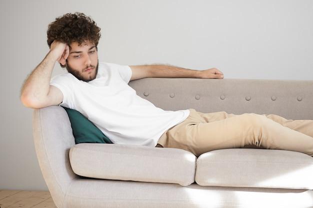 Menselijke gezichtsuitdrukkingen, gevoelens en emoties. horizontaal portret van knappe stijlvolle ongeschoren man in wit t-shirt en beige spijkerbroek verveeld en eenzaam voelen, tijd alleen thuis doorbrengen