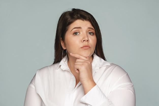 Menselijke gezichtsuitdrukkingen, gevoelens en emoties. nadenkend doordachte jonge europese zakenvrouw met grote bochtige lichaam haar kin aan te raken