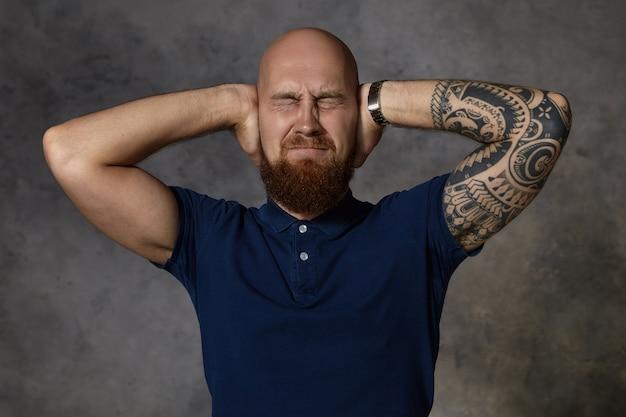 Menselijke gezichtsuitdrukkingen. horizontale opname van gefrustreerde geïrriteerde stijlvolle jonge getatoeëerde man met borstelige baard die de ogen gesloten houdt en de oren bedekt met een pijnlijke blik, gestrest door hard geluid