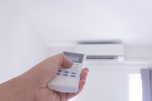 Menselijke hand die afstandsbediening voor airconditioner houdt om temperatuur te veranderen