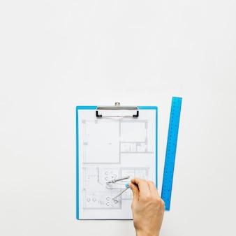Menselijke hand die blauwdruk maakt die rounder op wit bureau gebruikt