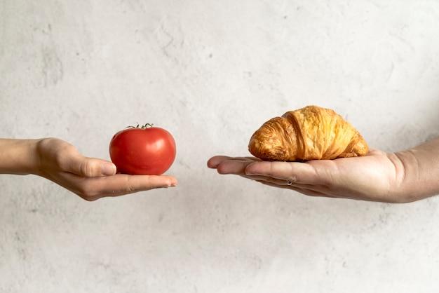 Menselijke hand die croissant en rode tomaat voor concrete achtergrond toont