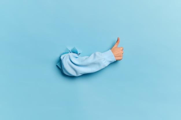 Menselijke hand die door document muur breekt en duim toont als teken van goedkeuring of overeenkomst.