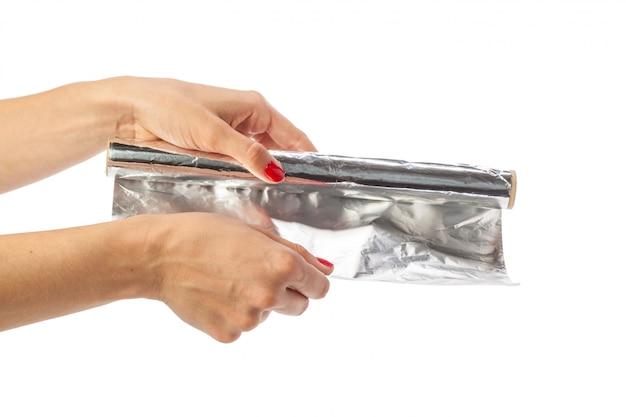 Menselijke hand die een broodje van folie op een witte achtergrond houdt