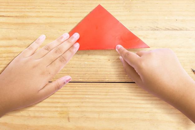 Menselijke hand die een houten achtergrond van gekleurd papier vouwt