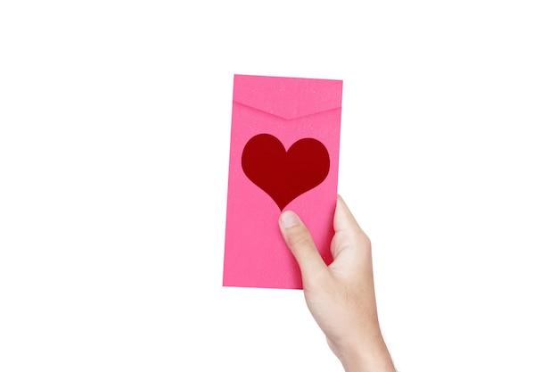 Menselijke hand die een roze envelop met hartvorm houdt die over witte muur wordt geïsoleerd