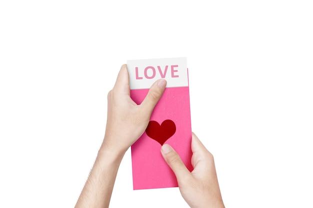 Menselijke hand die een roze envelop met hartvorm opent met liefdetekst op het document dat over witte muur wordt geïsoleerd