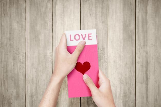 Menselijke hand die een roze envelop met hartvorm opent met liefdetekst op het papier op een houten muur. valentijnsdag