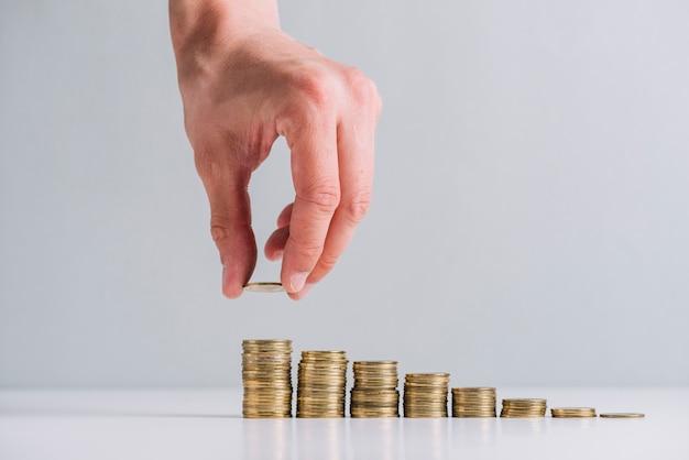 Menselijke hand die gouden muntstukken op weerspiegelend bureau stapelt