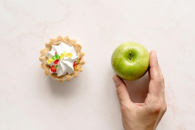 Menselijke hand die groene appel dichtbij scherpe cake over achtergrond houdt
