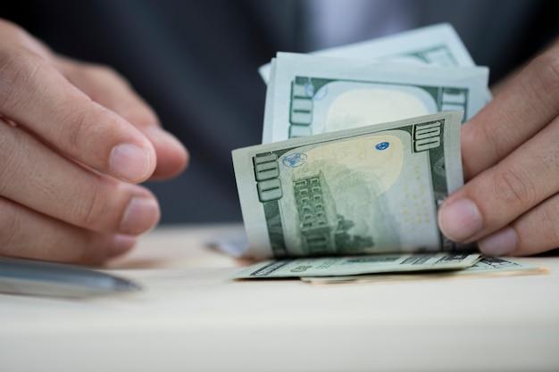 Menselijke hand die honderd amerikaanse dollarbankbiljet telt.