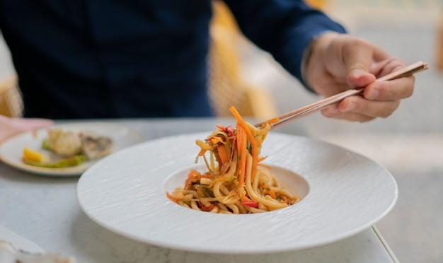 Menselijke hand die met stokjes de udon naar de groenten heft