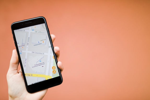 Menselijke hand die mobiele telefoon met kaartgps navigatie houden tegen oranje achtergrond