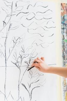 Menselijke hand die op canvas trekt dat houtskoolstok gebruikt