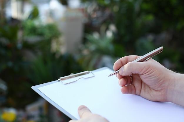 Menselijke hand die op klembord met witboek schrijft.