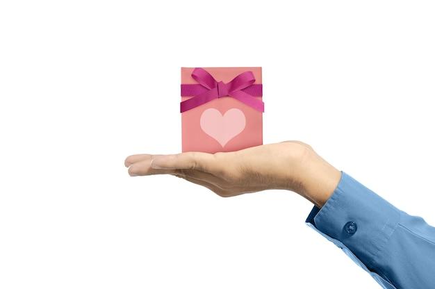 Menselijke hand die roze giftdoos met rood lint en hart toont dat over witte muur wordt geïsoleerd