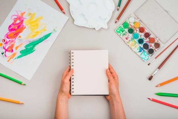 Menselijke hand die spiraalvormige blocnote met het schilderen van toebehoren over grijze achtergrond houdt