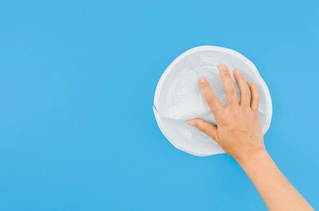 Menselijke hand die verfrommelde plastic plaat op blauwe oppervlakte houden