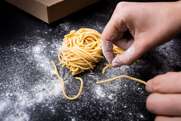 Menselijke hand die verse spaghettideegwaren voorbereidt met poederbloem op keukenteller