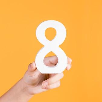 Menselijke hand die wit nummer 8 op een gele achtergrond steunt