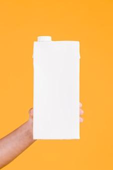 Menselijke hand die witte melkdoos op gele achtergrond houdt