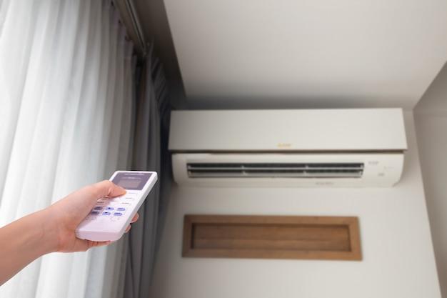 Menselijke hand dringende afstandsbedieningairconditioner in woonkamer, juiste copyspace.