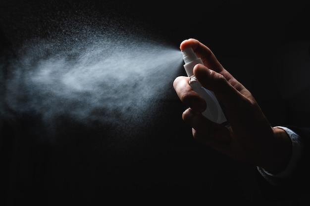 Menselijke hand en antiseptische spuitfles op donkere achtergrond. bestrijding van epidemische preventiemaatregelen van coronavirus.